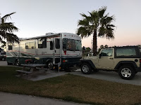 class A motorhome and Jeep in a campsite