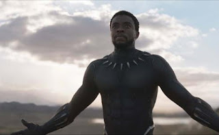 Chadwick Boseman as Black Panther, facing camera, looking towards the left with arms outstretched and a morning sky behind him