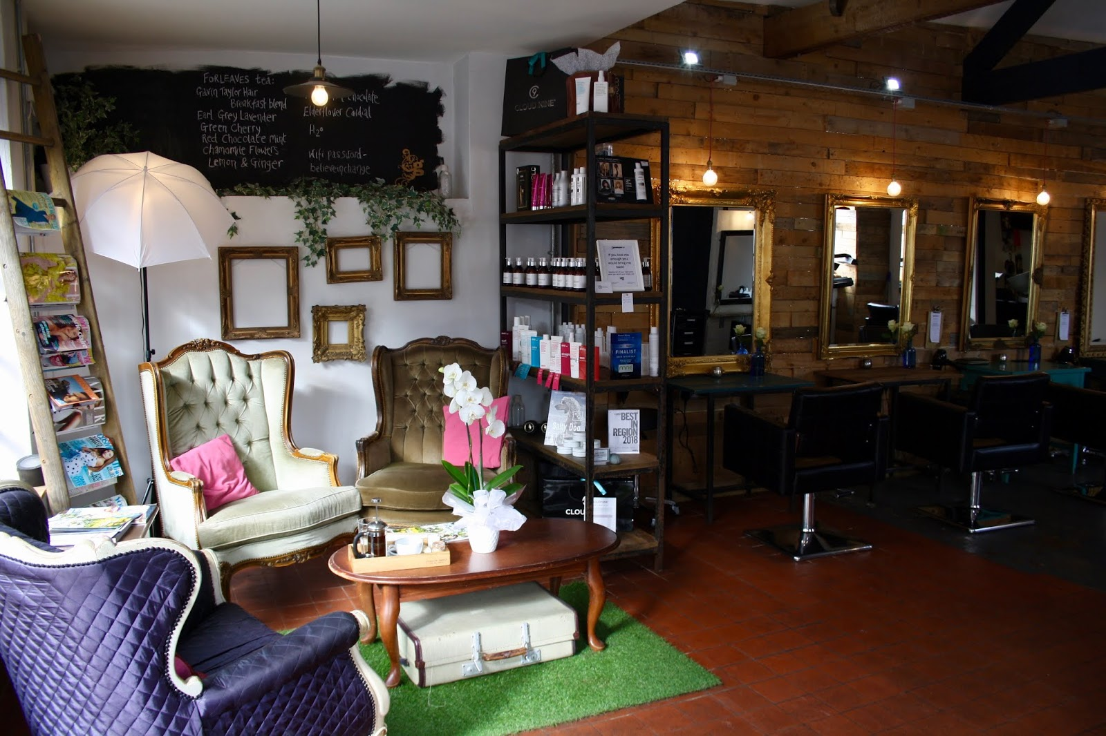 the reception area of the Gavin Taylor Hair salon, with vintage lounge chairs and a ladder used as a magazine rack