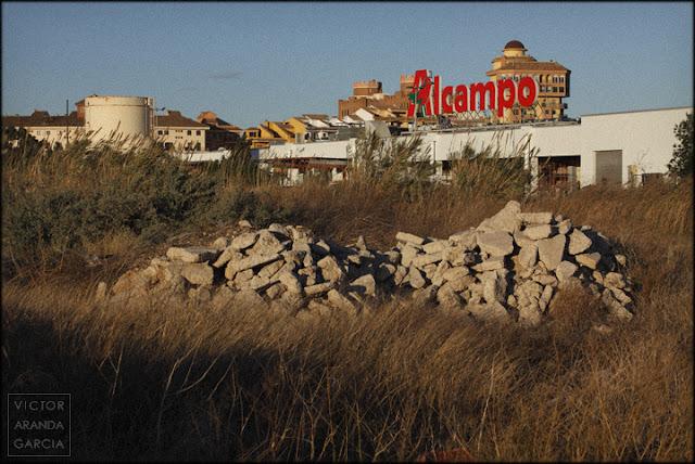 Fotografía de un centro comercial con montones de piedras delante