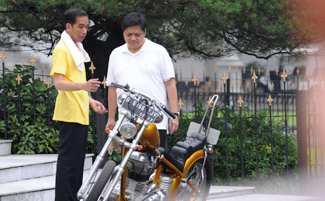 Presiden Joko Widodo menunjukkan motornya kepada Menteri Perindustrian Airlangga Hartato saat olahraga bersama di Istana Bogor