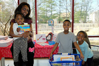 Family with Mom and 3 children holding books and Library Lovers Month postcards