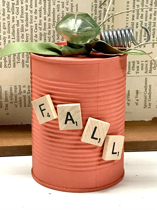 Scrabble letters on an orange pumpkin aluminum can