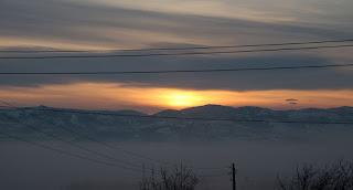 Mist in the valley, cloud above; sun in between