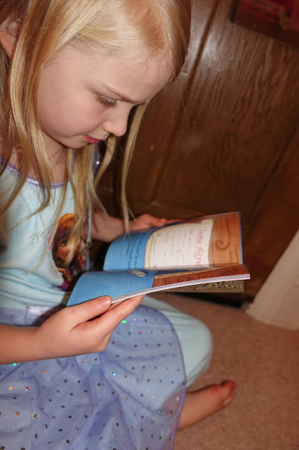 A young girl in a Frozen night dress reading a book (the Fairy Welcome Guide from the Irish Fairy Door Company)