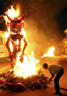 A large effigy of the Devil is burning in a bonfire.A man is bending down and adding something to the fire.