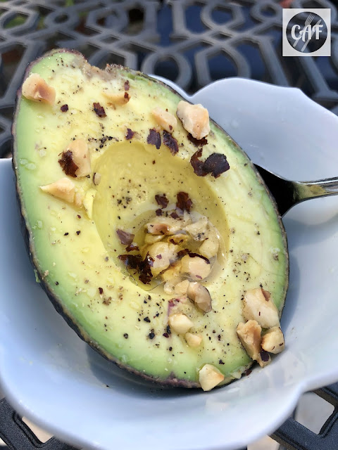 Avocado sprinkled with lime juice, toasted hazelnuts, olive oil, salt and pepper