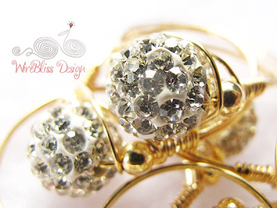Close up of sparkly wire wrap rings with 14k gold filled wire and beads