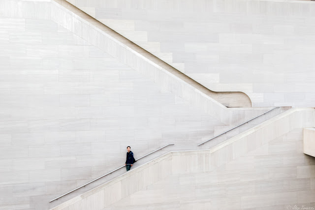 A man walking down the stairs at the National Gallery of Art in Washington, DC.