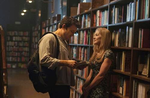 Ben Affleck as Nick Dunne in Gone Girl and Rosamund Pike as Amy Dunne in Gone Girl, getting cozy in a library, Directed by David Fincher