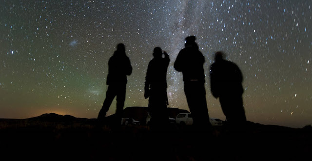 Four members of the observation team scan the sky while waiting for the start of the 2014 MU69 occultation, early on the morning of June 3, 2017. The target field was in the Milky Way, seen here from their observation site in the Karoo desert near Vosburg, South Africa. They used portable telescopes in an attempt to observe MU69, a small Kuiper Belt object (now nicknamed Ultima Thule) and the next flyby target of NASA's New Horizons spacecraft, pass in front of a star. New Horizons team members will attempt similar observations of Ultima this week in Colombia and Senegal. Credits: NASA/JHUAPL/SwRI/Henry Throop