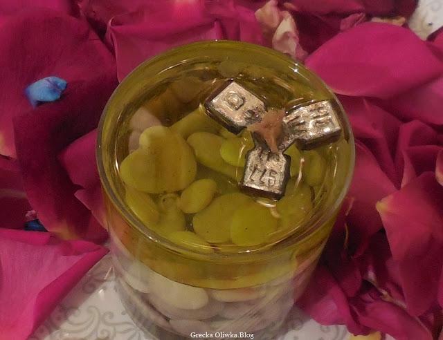 płatki róż pośrodku lampka oliwna z kamyczkami