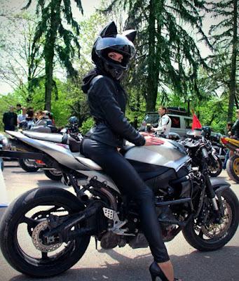 Mujer sexy  en moto con traje de cuero y casco negro con orejas felinas