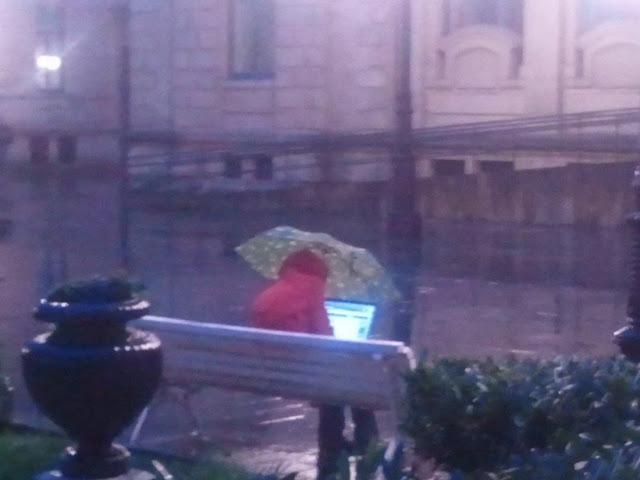 Guy using laptop under the rain