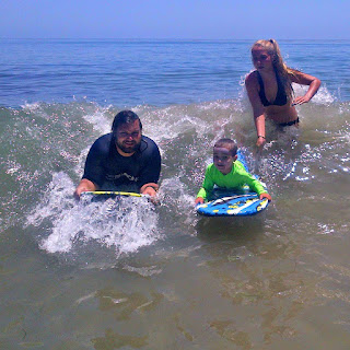 Keiki camp boy boogie boarding next to his camp counselors and camp director in the ocean at Paradise Cove