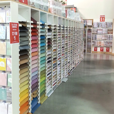 The inside of a scrapbooking paper factory outlet, with rows of paper on display.