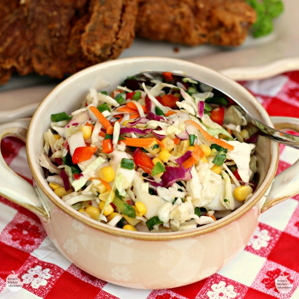 Firecracker Coleslaw by Renee's Kitchen Adventures in a bowl with fried chicken pieces on a white platter in background all sitting on a white and red checkered table cloth