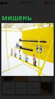 На улице стоит необычная мишень для тренировке по стрельбе на желтом фоне фигурки