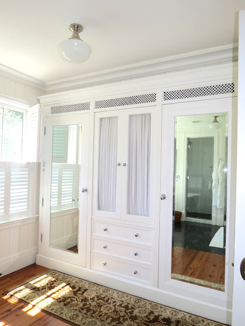 built in home closet with mirrors and drawers