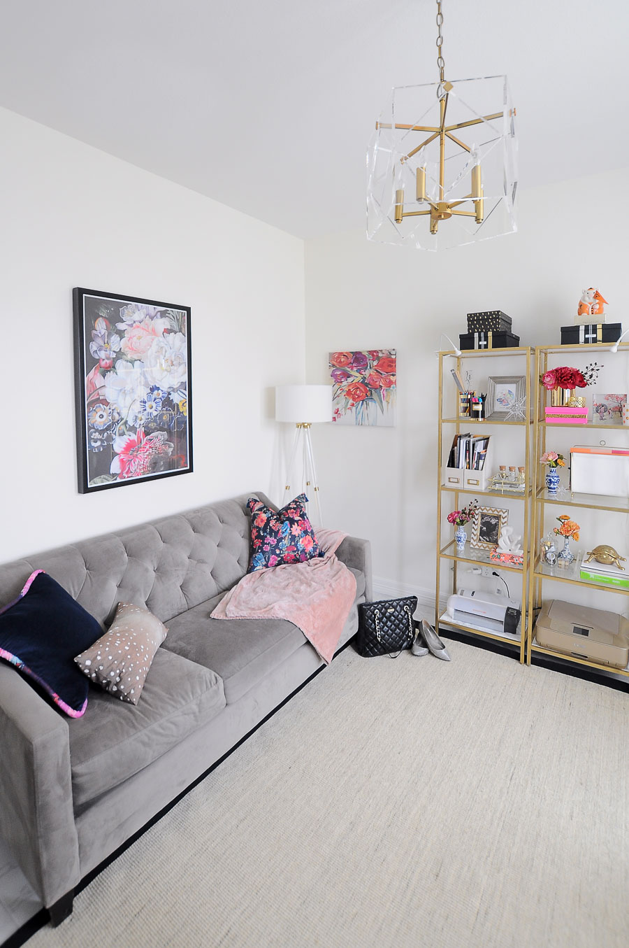 A gray tufted sofa in a feminine and chic home office space with tons of florals.