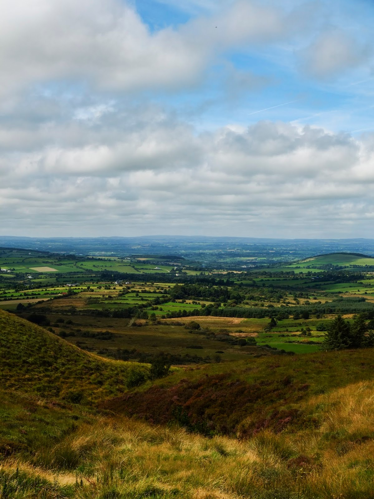 A mountain valley in North County Cork pictured on a sunny day with clouds.