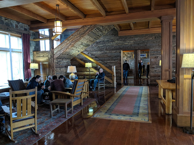 The lobby of the lodge has rustic rocking chairs and easy chairs as well a wooden staircase to the second floor.
