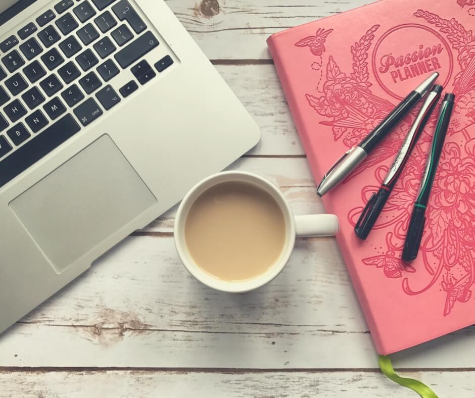 "A flatlay photo of a Macbook Air, a cup of tea, and an organiser. The Macbook Air is on the left of the photo, positioned diagonally, the cup of tea is in the centre of the photo, steam rising from the cup. A pink ""passion planner"" is on the right of the photo with birds engraved into its leather cover. Three pens sit on top of the planner, one blue, one black, and one red. Everything sits on top of a white wooden tabletop. Image for ""Teaching your children about online privacy""."