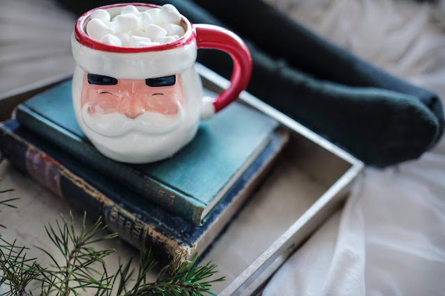 Cosy setting with a santa mug on a pile of books on a tray, and a pair of legs stretched out in the background