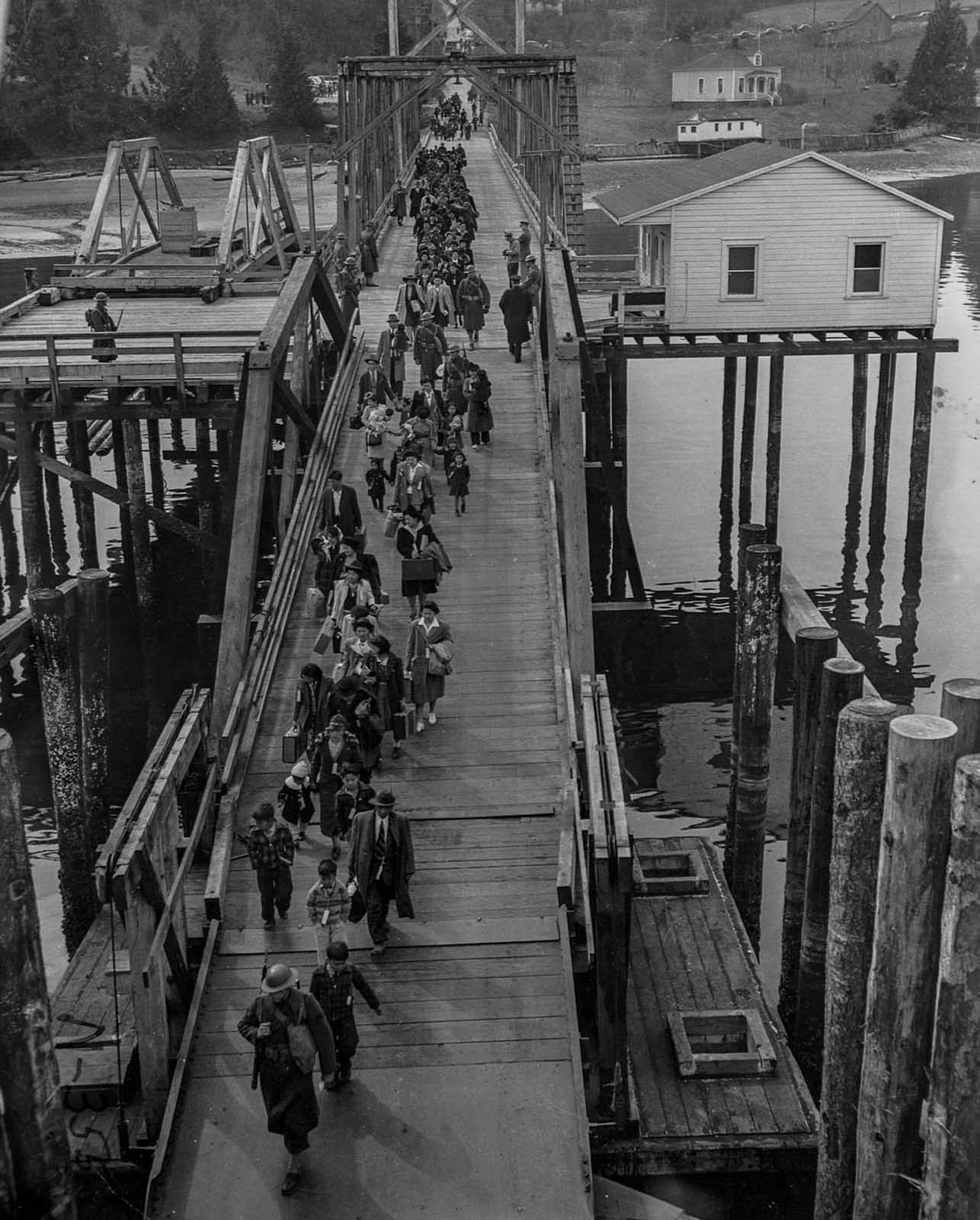 Japanese-Americans escorted by soldiers cross a bridge as they are evacuated from Bainbridge Island to be taken to a relocation camp.