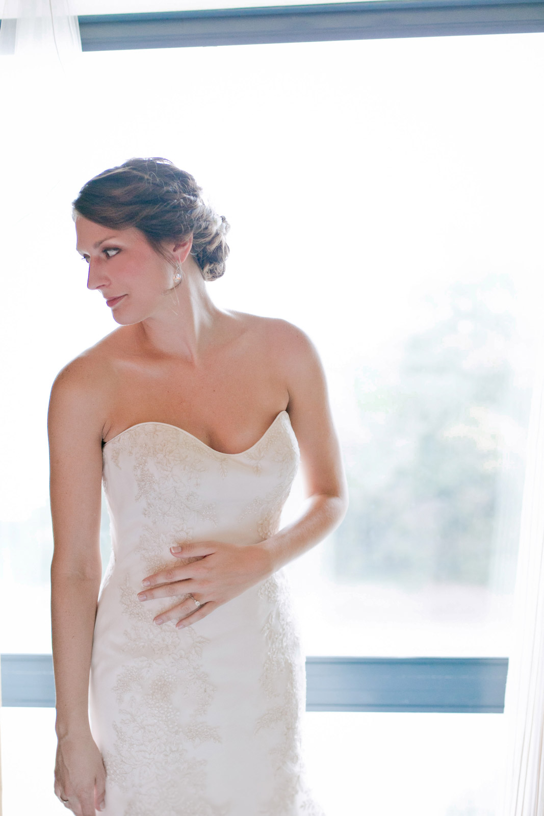 a bride stands by the window
