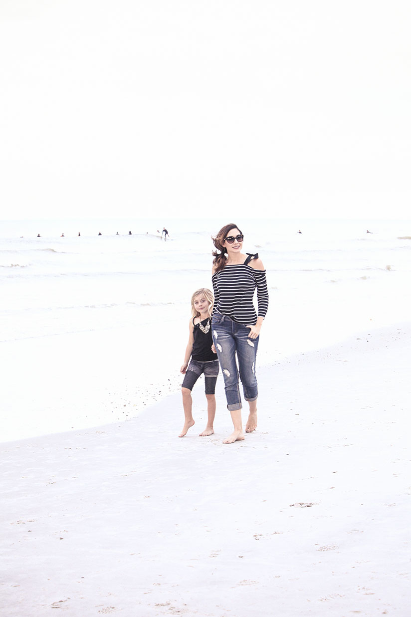 Amy West and daughter Sienna walk on the beach