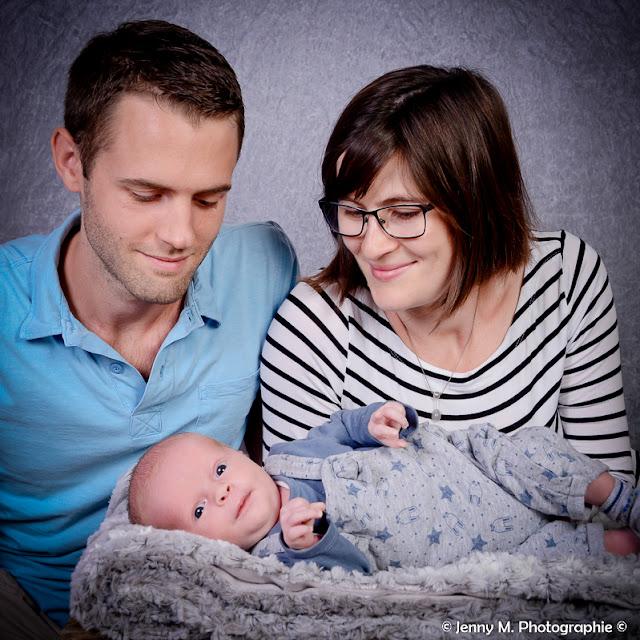 portrait de famille maman papa regardent bébé