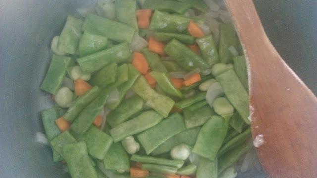 Judías verdes con zanahoria, fabas de mayo y cebolla en una olla para la cocción
