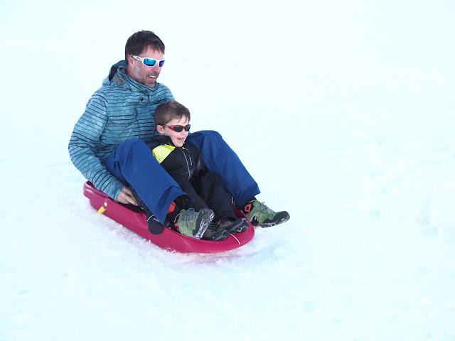 Padre e hijo lanzándose en trineo