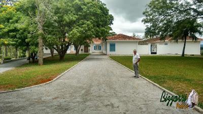 Piso de pedra com pedrisco cinza, com as guias de pedra em estrada da sede da fazenda em Atibaia-SP com o gramado com grama batatais e grama amendoim.