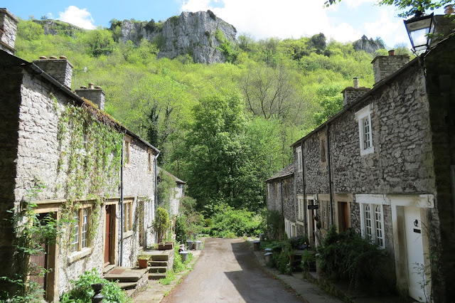 Looking between two rows of stone cottages that face each other. Woodland and crags in the background.