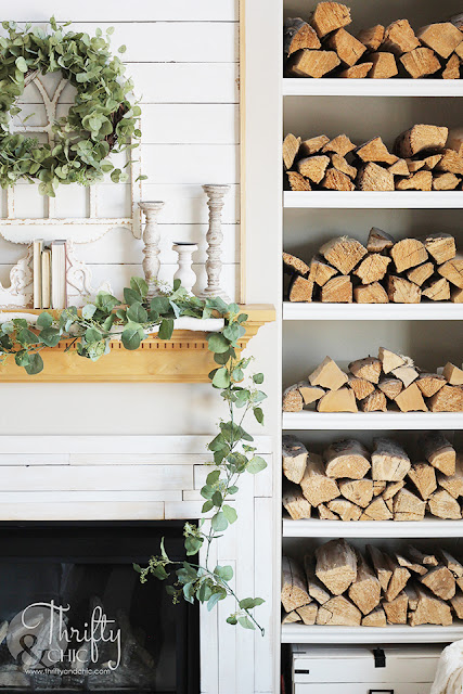knotty alder fireplace mantel with shiplap boards and eucalyptus wreath. Shelves filled with firewood