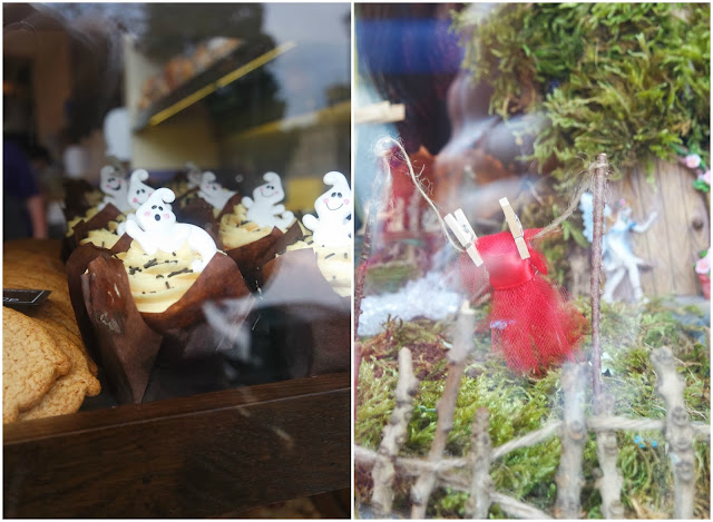 shop windows show a fair garden with a tiny red dress on a washing line above some moss, and a bakery selling cakes topped with ghost decorations