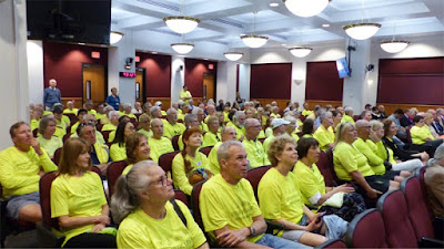 People with yellow shirts sitting at a local meeting in auditorium