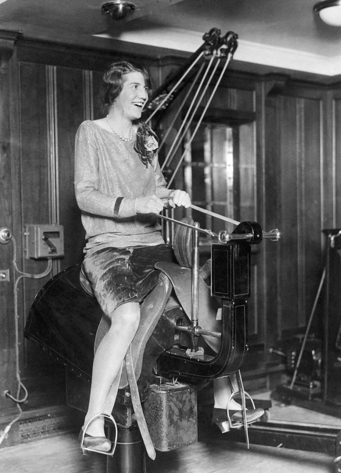 A young woman passenger riding the electric horse in the gym on the liner SS Bermuda. Mid 1920s.