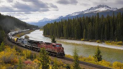 Un tren va recorriendo una sabana junto a un río y una montaña. Hay arbustos verdes y amarillos