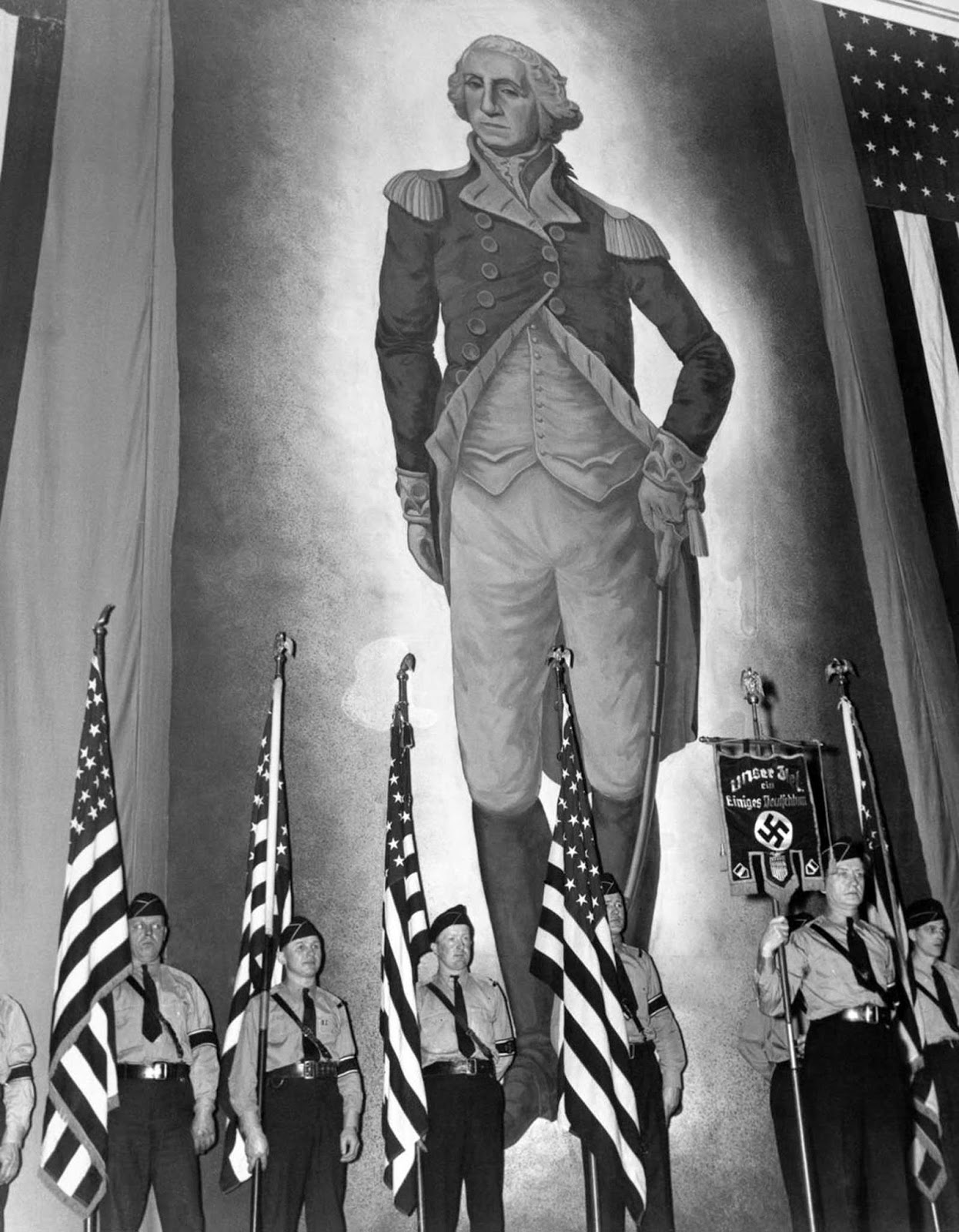 A Nazi guard stands before a massive portrait of George Washington.