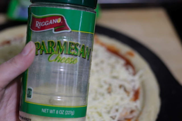 A canister of grated parmesan cheese about to be sprinkled over the pizza.