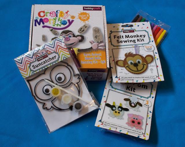 Photo of giveaway prize of: an owl suncatcher, farm animal nesting dolls painting kit, felt monkey sewing kit, pom pom kit and felt tips