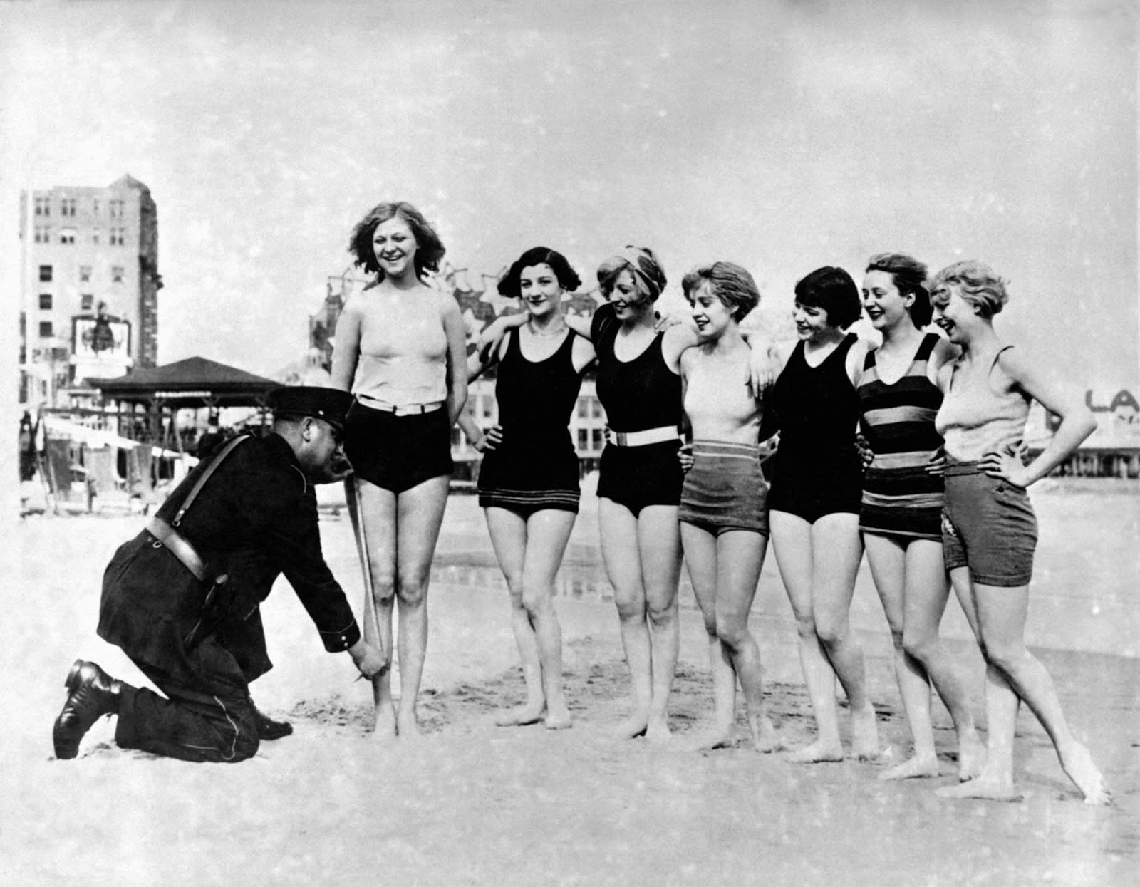 A policeman measuring the swimming costumes of women on the beach in the 1920s.