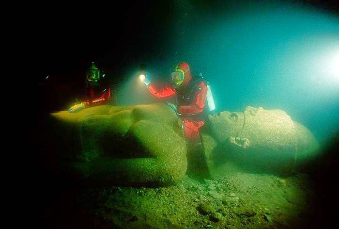 Franck Goddio and divers of his team inspecting the statue of a pharaoh found close to the big temple of sunken Heracleion.