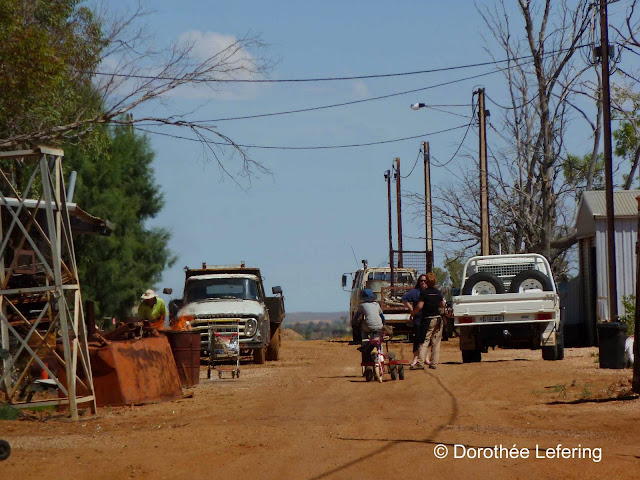 An old lorry, a child on a bicycle, two women chatting on a red unpaved road.