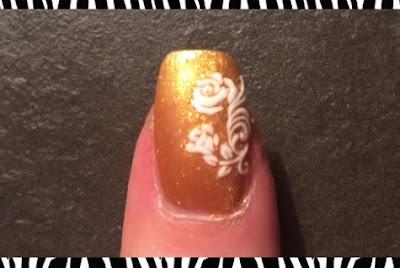 molto elegantemente rappresentata la nail art con adesivi bianchi in rilievo su una mano oro