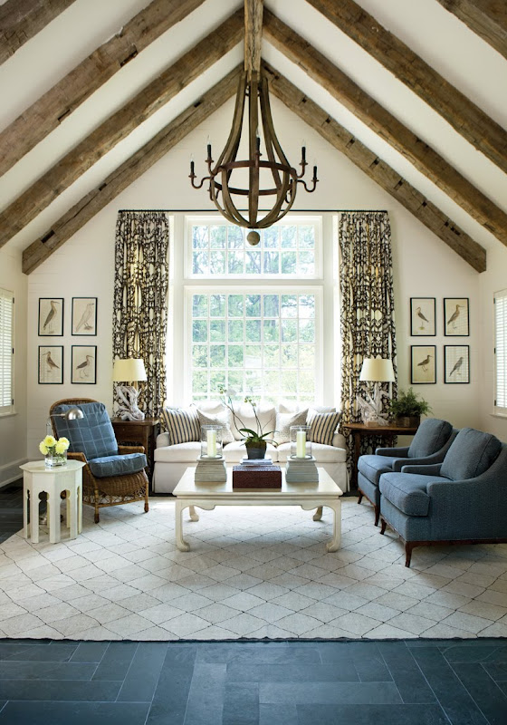 Living room in a pool house with high beamed ceiling, wine barrel chandelier, slate floors, diamond patterned white rug, blue armchairs, a white sofas, graphic print curtains, a white coffee table and one brown armchair