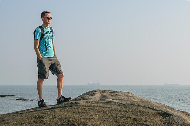 Homme scrutant l'horizon sur la plage de Xiamen